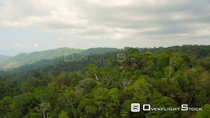Flying low over dense jungle forests panning to large bay views. Costa Rica