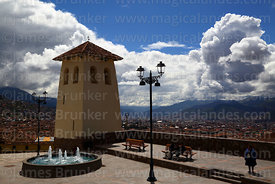 Santa Ana church belfry and Plaza Santa Ana, storm clouds above city in distance below, Cusco, Peru