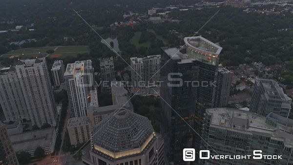 Atlanta Midtown cityscape birdseye fly over toward hot air balloons at Piedmont park at dusk