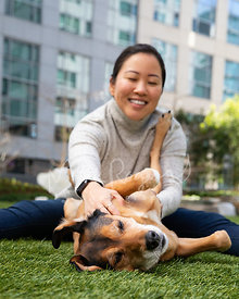 Woman on Ground Pets Dog on its Side