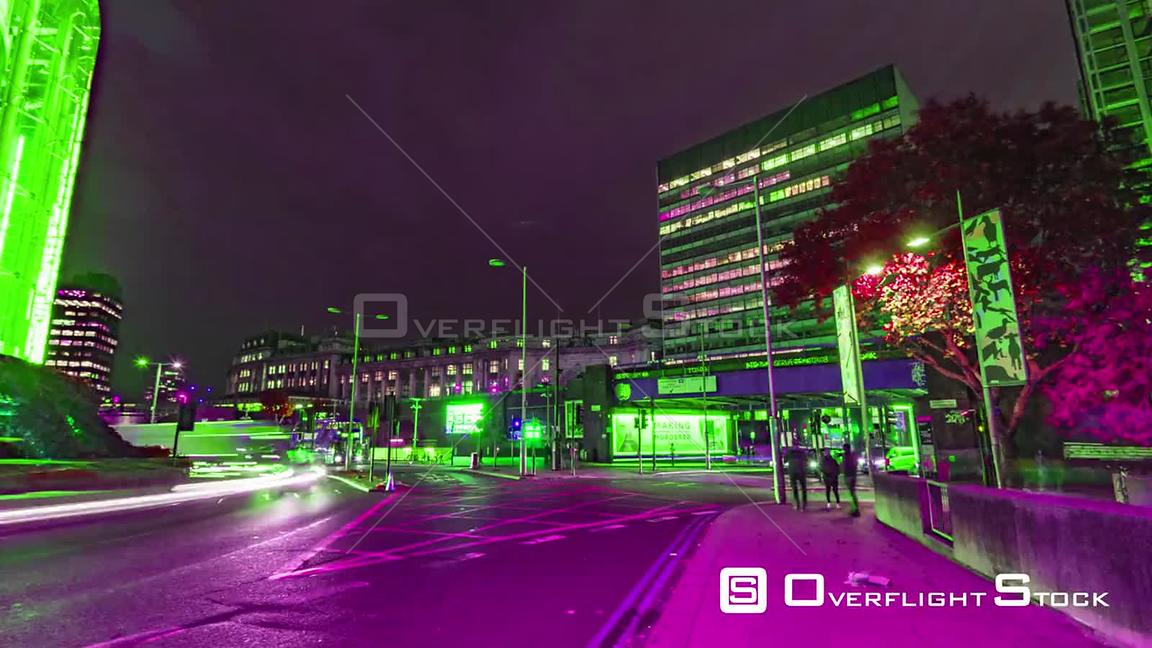 Timelapse view of a busy crossroad near Waterloo station in London at night with lights shifting color