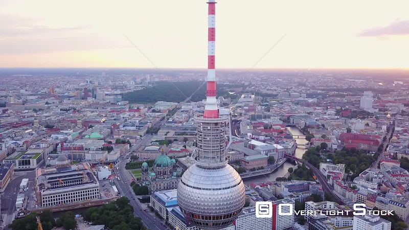 Germany Berlin Aerial Flying low around Berliner Fernsehturm tower cityscape views sunset