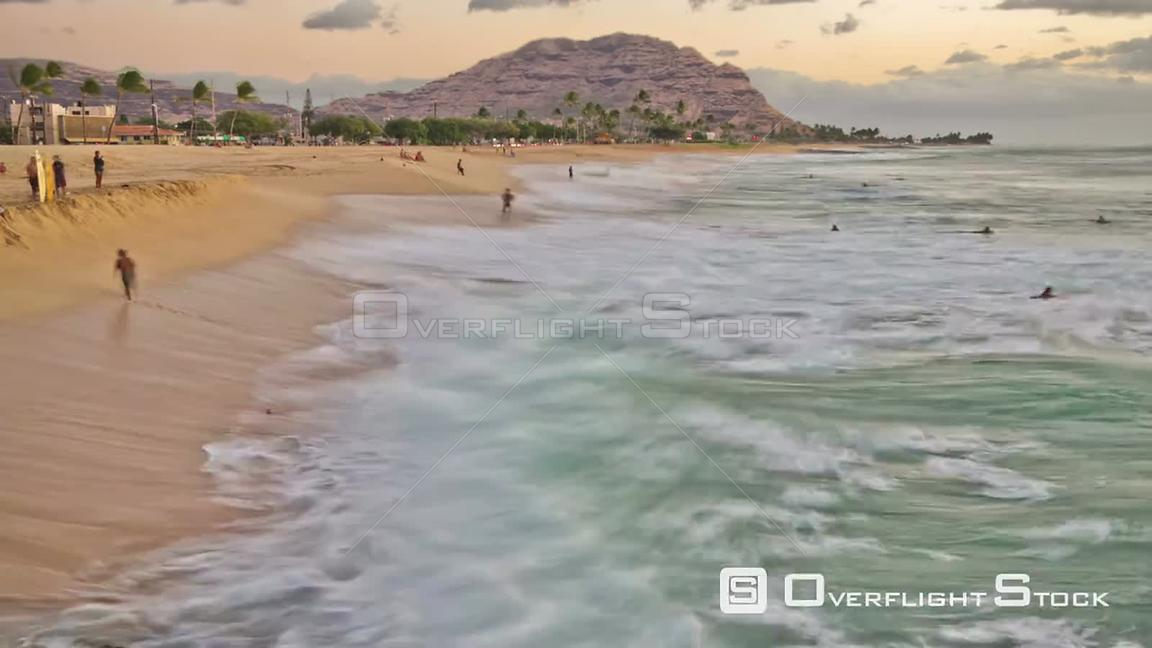 Beautiful time lapse clip during sunset of people playing on beach. Hawaii