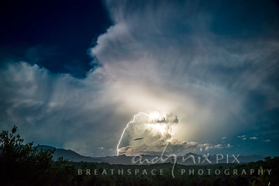 Lightning storm at night over mountains and forest