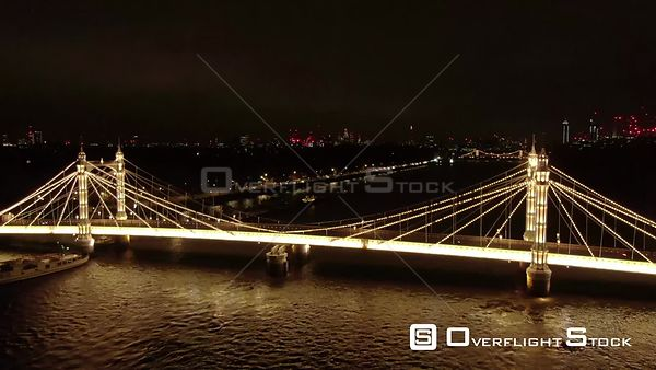 A car driving on Albert Bridge, filmed by drone in autumn, at night, London, United Kingdom