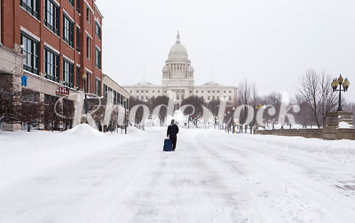 Man walks towards the Rhode Island State House in the snow.