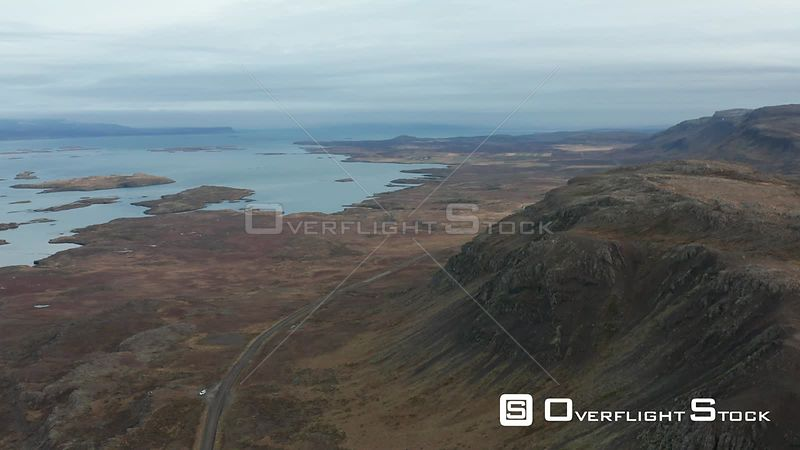 Flying Along the Coast Over a Road and Mountains in Iceland.