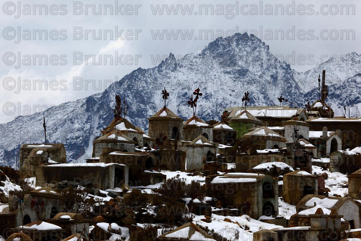 Tombs on hillside in Milluni cemetery after winter snowfall, Cordillera Real, Bolivia
