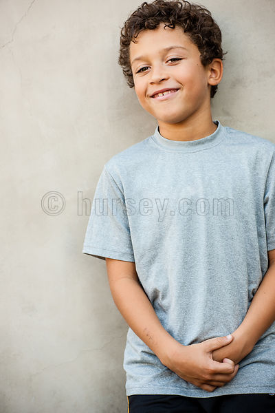 image of a mixed race child / boy against a mottled grey wall wearing a grey t-shirt.