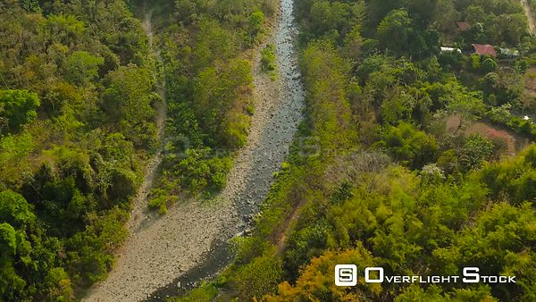 Flying low over small river in jungle forest looking down. Costa Rica