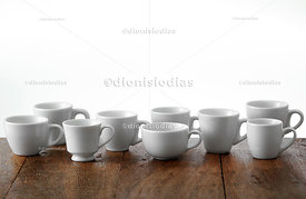Coffee cup models on wooden background.