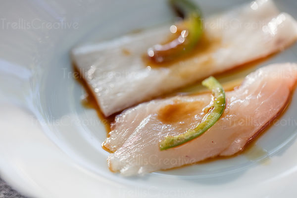 Close up of a plate of fresh yellowtail tuna sashimi.