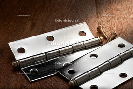 Metallic hinges in close on a wooden background