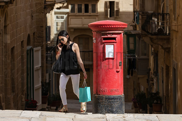 Woman on Phone Walking Past an Old English-Style Pillar Box