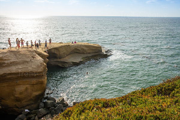 Teen girl jumps off beach cliff into water, Point Loma, Ocean Beach, San Diego, California, USA.
