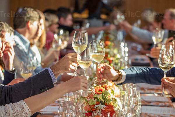 Three glasses being raised at a formal celebration.