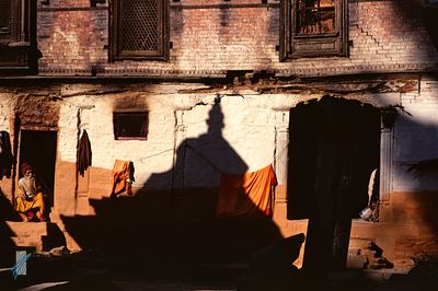 A sadu sits in the sun outside his home