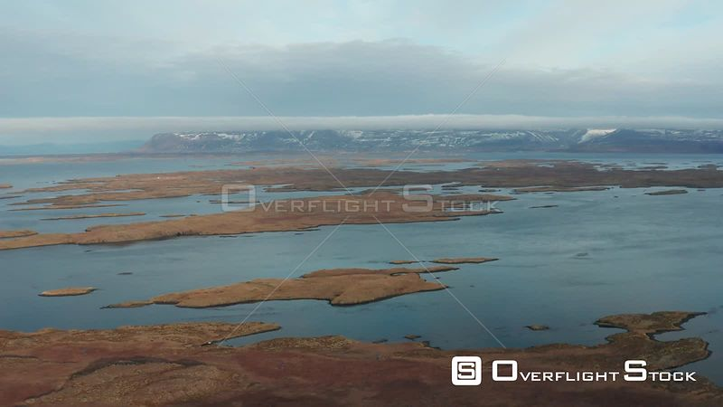 Flying Over Islands in a Bay With Snow Covered Mountains Behind in Iceland.