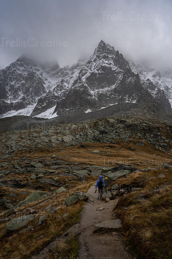 A young woman hikes a rocky mountain trail in the French Alps