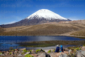 Tourists looking at view across lagoon to Parinacota volcano, Lauca National Park, Region XV, Chile