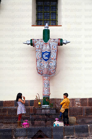 Children praying to cruz velakuy cross next to Santa Ana church, Cusco, Peru
